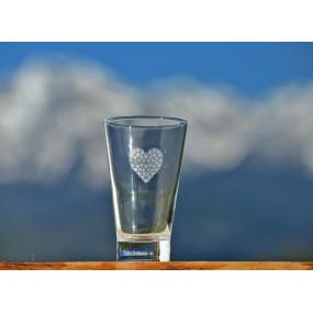 White heart of flowers on orange juice glass